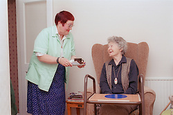 Carer giving elderly woman cup of tea smiling,