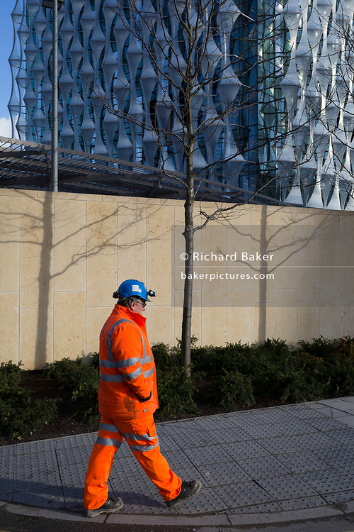 A construction worker walks past the US Embassy at Nine Elms in south London, on 16th January 2018, in London, England. On the day when the consulate opened for public business (visa applications etc.)  after its controversial move from Grosvenor Square in central London to the south bank.