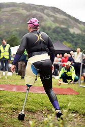 A disabled woman cliimbs out of the water at an Open Water Swimming Event Ullswater lake, Cumbria UK in her wetsuit.