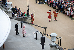 Queen Elizabeth II and the Duke of Edinburgh arrive to greet guests at a garden party at Buckingham Palace in London.