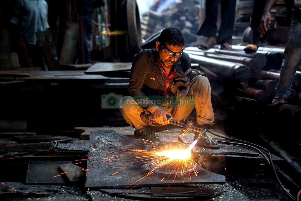 June 5, 2017 - Dhaka, Dhaka, Bangladesh - June 05, 2017 Dhaka, Bangladesh - A man cutting a sheet of steel by the gas cylinder at roadside of Metal factory in Dhaka. This workers work in a limited workplace in often-overcrowded conditions and without much in the way of safety equipment. Working in a Metal factory without masks or proper gloves exposing them to the risk of accidents or health problem. (Credit Image: © K M Asad via ZUMA Wire)