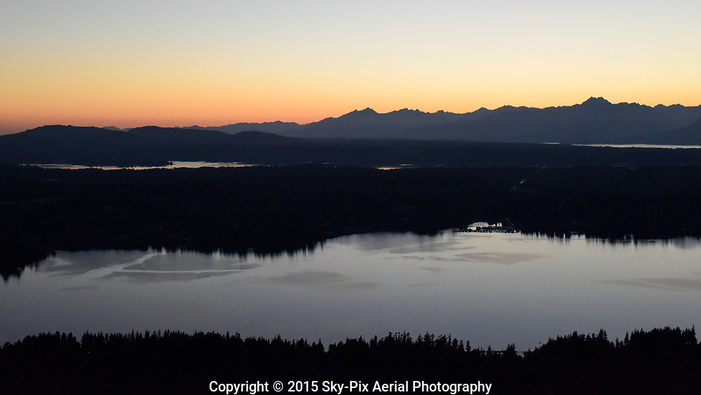 Sunset aerial photo taken from over Bainbridge Island, looking across Port Orchard Bay to Brownsville, with the Olympic Mountains in the background.