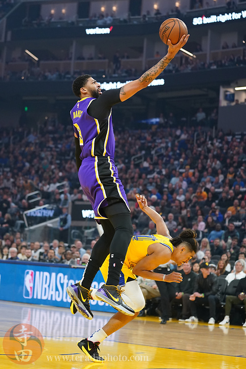 February 27, 2020; San Francisco, California, USA; Los Angeles Lakers forward Anthony Davis (3, top) shoots the basketball against Golden State Warriors guard Jordan Poole (3, bottom) during the first quarter at Chase Center.