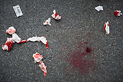 Traces of paper and blood seen on the ground during street procession in Phuket town. Every year during the ninth lunar month of the Chinese calendar, the Phuket Vegetarian Festival kicks off. The religious festival in Phuket, Thailand, lasts for 10 days, during which sacred rituals take place in the many Chinese shrines and temples. Walking on fire and climbing ladders with bladed rungs barefoot are two of several rituals believed to bring good fortune. The main purpose of the festival, however, is spiritual cleansing and merit-making. A chosen few among the participants, called warriors, will pierce themselves with objects such as nails, swords, and knives. The piercing takes place in a shrine and is followed by the most spectacular part of the festival, the street processions: just like in a parade they file along the streets of Phuket, with groups of one or several pierced warriors leading a number of people behind them. Onlookers throw fireworks at them as they pass; these are intended to be as loud as possible as the common belief is that this will banish evil spirits. The warriors walk and dance in a trance-like state, unshaken by the noise.