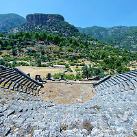 The 2nd century BC theatre. In the background is the red cliff which contains thousands of rocks cut tombs. Pinara. Turkey. The Greek styled theatre is situated at the base of the city and accommodated up to 3,200 spectators. The great red cliff which rises to a height of 500 metres and has thousands of rocks tombs and caves cut into the vertical cliff face.