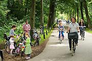 Bij Rhijnauwen zet een gezin de fietsen neer bij het pannenkoekenrestaurant, terwijl een ander gezin voorbij komt fietsen. Mensen genieten van het mooie weer, door te wandelen, te fietsen of een pannenkoek te eten bij het pannenkoekenrestaurant.<br /> <br /> Near Rhijnauwen a family is parking their bikes, while another family is cycling by. People are enjoying the nice weather by walking, cycling or eating pancakes.