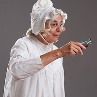An old woman in a night gown and cap, pouring poison from a small apothecary bottle.