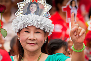 01 JULY 2011 - BANGKOK, THAILAND:  A woman wears a hat showing a likeness of Yingluck Shinawatra, the Pheua Thai candidate for Prime Minister, during a Pheua Thai rally in Bangkok Friday. Thailand's divisive election campaign drew to a close Friday in Bangkok. Most of the parties had large rallies in an effort to sway last minute undecided voters. Pheua Thai, the party of ousted Prime Minister Thaksin Shinawatra held a massive rally in Rajamakala Stadium (also called Ramkamhaeng Stadium) to close out their campaign. A monsoon thunderstorm didn't keep people away from the event. Most Thai public opinion polls show Pheua Thai with a healthy lead over their arch rivals (and incumbent party in power) the Democrats. Thaksin's youngest sister, Yingluck Shinawatra, is running for Prime Minister under the Pheua Thai banner. If elected, she will be Thailand's first female Prime Minister.      PHOTO BY JACK KURTZ