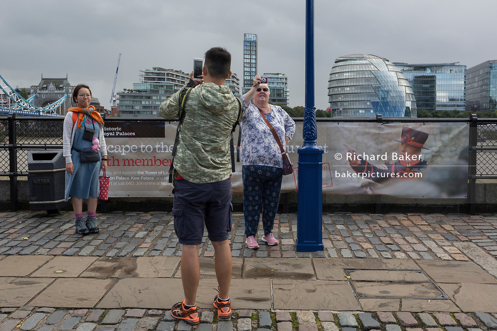 Tourists photograph an unseen Tower Bridge near the image of a Beefeater on a railing in front of the Tower of London, on 14th September 2017, in London, England.