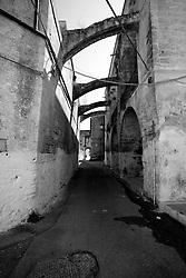 Inoltrandoci per le vie del centro storico di Lizzano (Ta), possiamo scoprire la parte nascosta del castello. Questa veduta in particolare ci mostra la parte laterale-posteriore del castello. La struttura sulla destra rappresenta il castello, mentre quella sulla sinistra è la Chiesa del Rosario. Le due strutture sono unite da arcate che vennero costruite a causa di un terremoto avvenuto a metà del 1700.