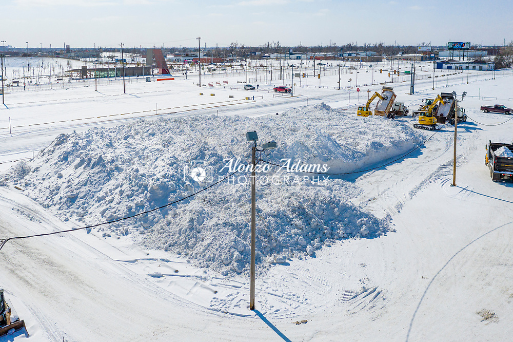 Oklahoma City crews move snow from downtown streets and place it in a parking lot just west of Chesapeake Energy Arena on Monday, Feb. 15, 2021. Photo copyright © 2021 Alonzo J. Adams.