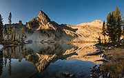 A peak reflects in Twin Lakes at sunrise in Sawtooth Wilderness, Blaine County, Idaho, USA. in Sawtooth Wilderness, Blaine County, Idaho, USA. On October 6-7, 2020, starting from Tin Cup Trailhead, I hiked the Alice-Toxaway Loop clockwise for 20 miles including an overnight stay at idyllic Twin Lakes. The first day to Twin Lakes was a moderate 7.4 miles with 2090 feet gain. The second day returned via Toxaway Lake and Farley Lake for 12.5 miles with 1260 feet up and 2940 feet down. For the most dramatic scenic build-up, I recommend backpacking 3 days counterclockwise staying at Toxaway Lake then Twin Lakes. (On a 2007 backpacking trip in August, we enjoyed staying 2 nights at Alice Lake and day-hiked to Toxaway.) The Sawtooth Range (part of the Rocky Mountains) are made of pink granite of the 50 million year old Sawtooth batholith. This image was stitched from multiple overlapping photos.