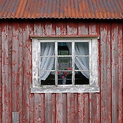 A window of a red-painted rorbu fisherman's cabin on 25th August 2016 in Lofoten, Norway. The Lofoten islands are famous for their jagged mountains, red-painted rorbu cabins and racks with fish hanging closely packed to dry.