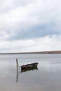 A waterlogged boat moored by a beach, Weymouth, Dorset, United Kingdom.