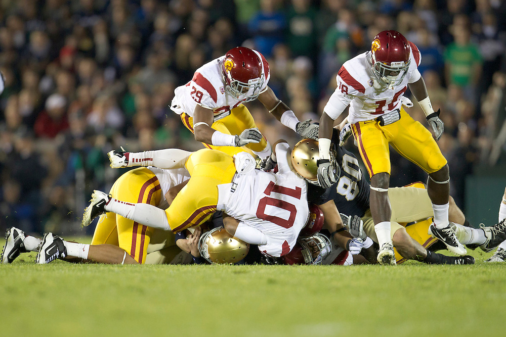 Notre Dame quarterback Andrew Hendrix (#12) is tackled by USC defenders during second quarter of NCAA football game between Notre Dame and USC.  The USC Trojans defeated the Notre Dame Fighting Irish 31-17 in game at Notre Dame Stadium in South Bend, Indiana.