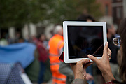 Woman with an iPad takes pictures at Occupy London demo and feeds them back via skype to her daughter back in the US.