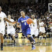 Memphis guard Charles Carmouche (4) drives past Central Florida forward Keith Clanton (33) during a Conference USA NCAA basketball game between the Memphis Tigers and the Central Florida Knights at the UCF Arena on February 9, 2011 in Orlando, Florida. Memphis won the game 63-62. (AP Photo: Alex Menendez)
