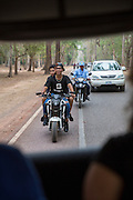 A young Cambodian man smiles whilst riding his motorbike along a road with other cars and bikes n Krong Siem Reap Province, Cambodia, South East Asia.  Photo taken from the back of a tuck tuck. (photo by Andrew Aitchison / In pictures via Getty Images)