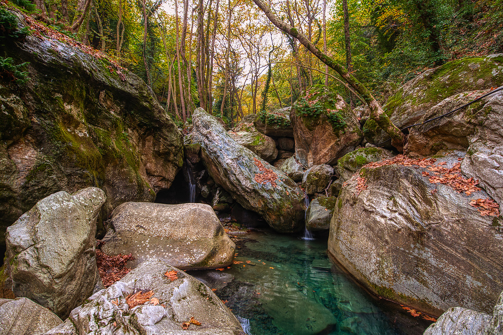 Small creek between boulders in the forest in Pelion, Greece.