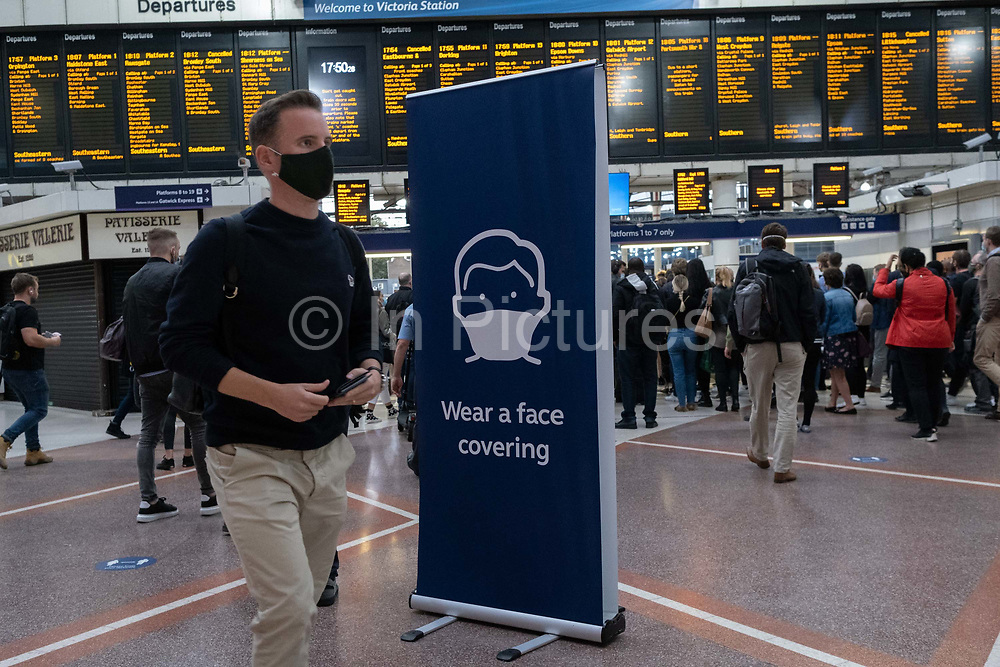 A large sign stands on the concourse of Victoria railway mainline station urges passengers and commuters to wear a face covering while travelling on the capital's public transport system, on 24th September, in London, England. New restrictions are being re-introduced by the government after a sudden climb in the Covid infection rate, a predicted 'second spike'. Only those who have medical or psychological issues are exempt from wearing a face covering although £200 fines are in place for those flouting rules.
