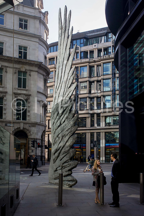 City workers talk under the giant artwork of a bronze wing during lunchtime on Threadneedle Street in London's financial district known as the Square Mile. As light reflects off nearby office buildings, the lunchtime crowd walk past this giant artwork on their way to meetings and sandwich bars. The ten-metre-tall bronze sculpture is by President of the Royal Academy of Arts, Christopher Le Brun, commissioned by Hammerson in 2009. It is called 'The City Wing' and has been cast by Morris Singer Art Founders, reputedly the oldest fine art foundry in the world.