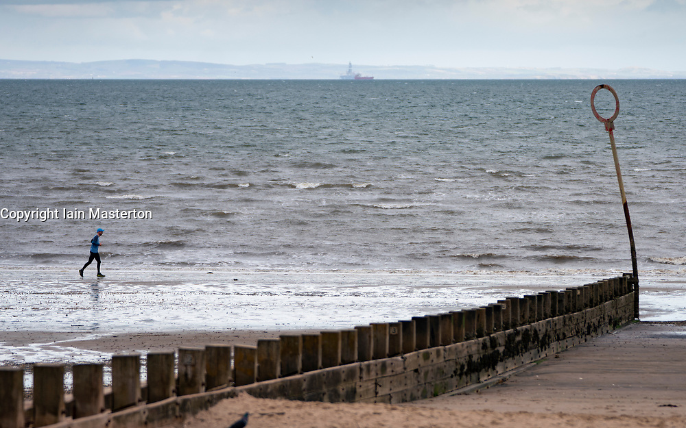 Portobello, Scotland, UK. 28 March, 2020. On the first weekend of the coronavirus lockdown the public were outdoors exercising and maintaining social distancing along Portobello beachfront promenade. Pictured; Runner on beach.  Iain Masterton/Alamy Live News