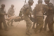 US soldiers carry a comrade from 1-320th Alpha Battery, 2nd Brigade of the 101st Airborne Division, to a medical evacuation helicopter after he was seriously wounded by stepping on an improvised mine near COP Nolen, in the volatile Arghandab Valley, Kandahar, Afghanistan, Friday, July 29, 2010. (AP Photo/Rodrigo Abd)