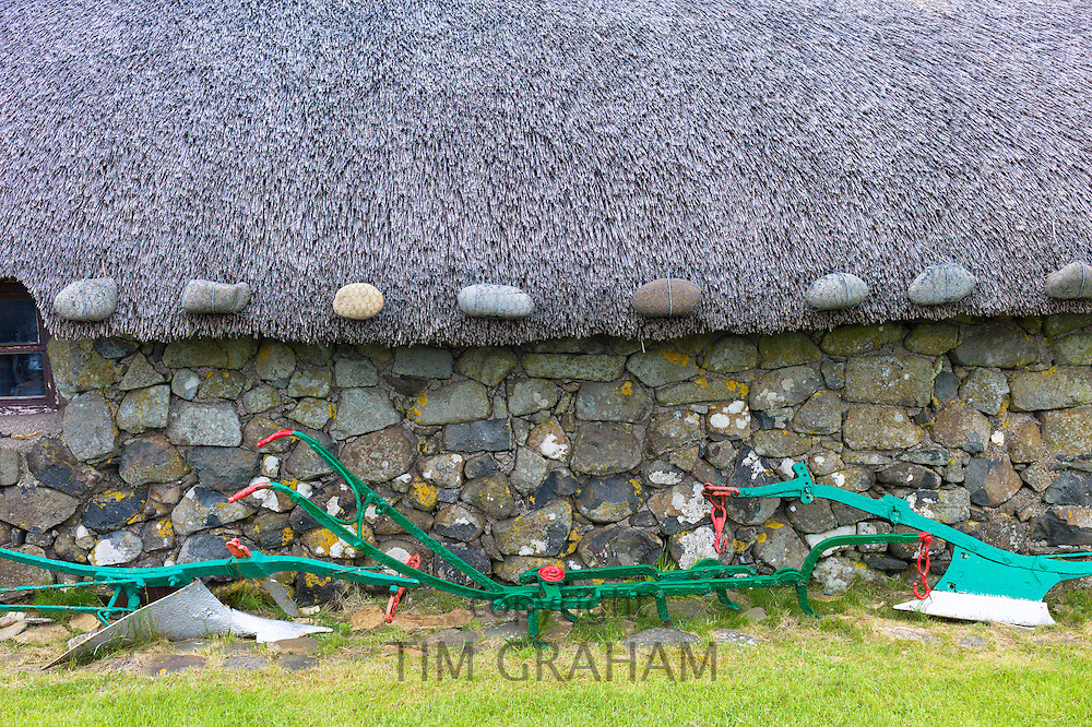 Tourist attraction Skye Museum of Village Life depicts thatched stone barn with old plough and farm implements at Kilmuir, Isle of Skye, the Western Isles of Scotland, UK