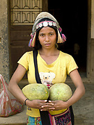 Portrait of a young Akha Ya-er woman wearing her traditional headdress selling cucumbers that she has grown herself at Pak Nam Noi market, Phongsaly province, Lao PDR. One of the most ethnically diverse countries in Southeast Asia, Laos has 49 officially recognised ethnic groups although there are many more self-identified and sub groups. These groups are distinguished by their own customs, beliefs and rituals. Details down to the embroidery on a shirt, the colour of the trim and the type of skirt all help signify the wearer's ethnic and clan affiliations.