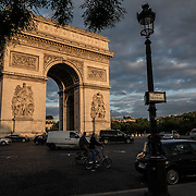 The Arc de triomphe in Paris during the golden hour.