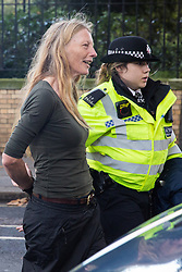 London, UK. 13 October, 2019. Police officers arrest a climate activist from Extinction Rebellion using Section 14 of the Public Order Act 1986 during a protest outside New Scotland Yard against tactics employed by police officers which impinge on the right to protest of disabled activists, including the confiscation of wheelchairs, wheelchair ramps, accessible toilets and tents.