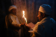In many Ethiopian churches carved into the rock the reading of sacred texts is still done with the help of wax candles.<br /> In this scene we can see the exchange of candles between two Deacons to allow the reading and recitation of the text to continue.<br /> In the Ethiopian Orthodox church, candlelight would also symbolize divine light.