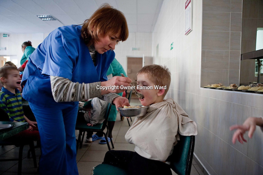 Feeding a child at the Vesnova Childrens Mental Asylum,Belarus. Chernobyl's human costs are widespread affecting about seven million people. A generation later children are being born with birth defects ,heart problems and thyroid cancer.The crippled economy of Belarus has led to poverty, social problems and domestic abuse.