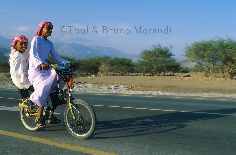 Emirats Arabe Unis. Emirat de Fujairah. // United Arab Emirates. Fujairah Emirate. Boys on bike.