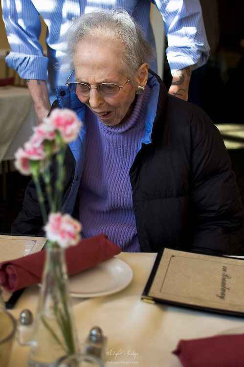 My brother helping mom get herself up to the table on her 90th birthday for a celebration dinner.