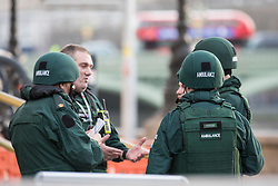 © Licensed to London News Pictures. 22/03/2017. London, UK. Paramedics wearing body armour wait by the London Eye after a man ran down a number of pedestrians on Westminster Bridge before entering Westminster Palace. Police are treating the incident as a terrorist attack. Photo credit: Rob Pinney/LNP