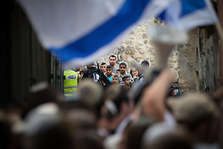 © Licensed to London News Pictures . 05/06/2016 . Jerusalem , Israel . Israeli soldiers separate residents of the Old City's Muslim district from thousands of Jews with flags processing through the Old City's Muslim district , on the way to the Western Wall . Israeli Jews celebrate Jerusalem Day . Photo credit : Joel Goodman/LNP