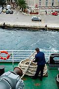 Sailor stowing rope, inter-island ferry leaving island of Korcula, Croatia