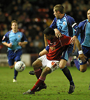 Photo: Dave Linney.<br />Walsall v Barnsley. The FA Cup. 17/01/2006.<br />Walsall's Kevin James (L) fends off the challenge of Paul Reid.