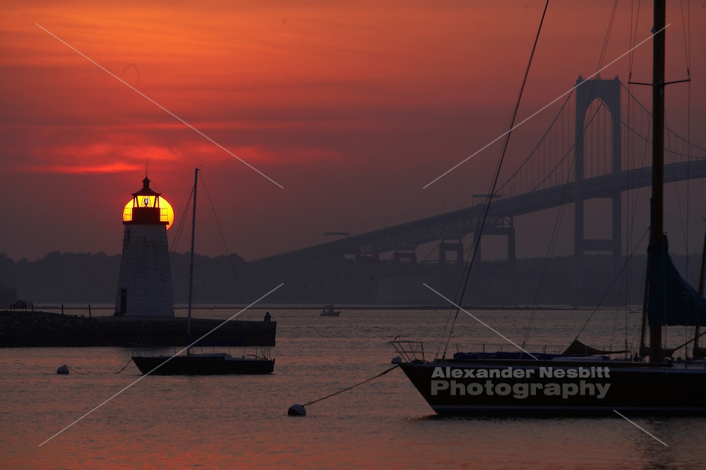 Newport, RI - Sunset behind goat island light house with boats on moorings in the point sectin of Newport.