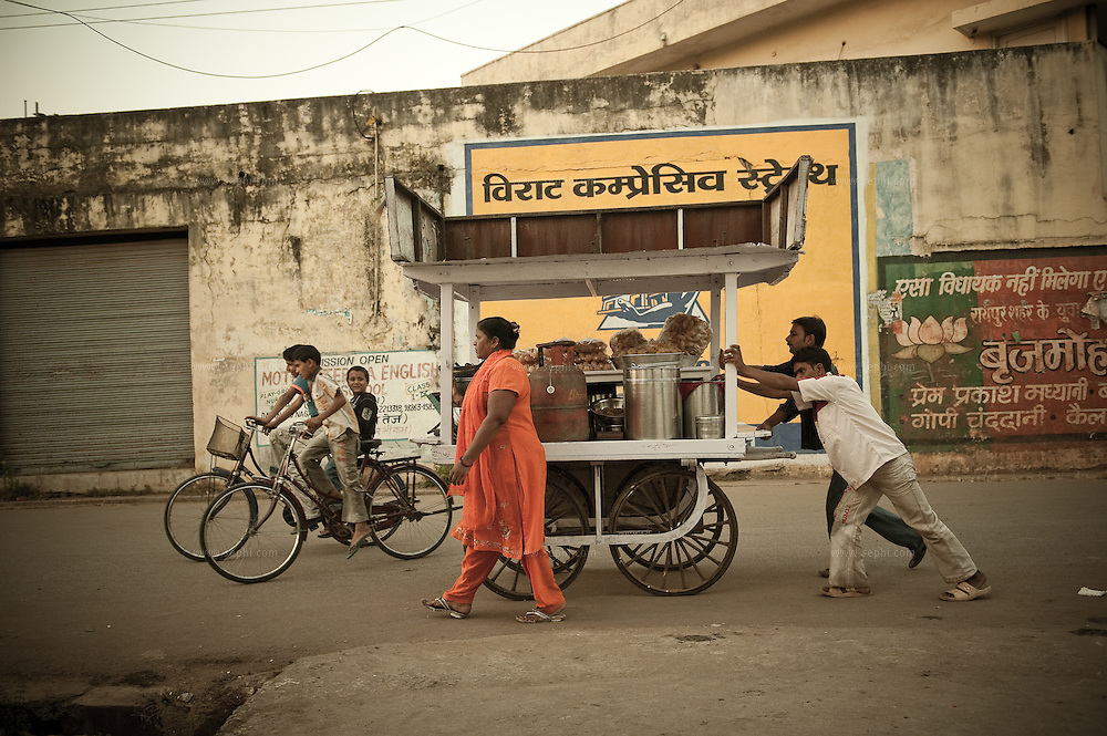 Devo Baghel (48. in Orange suit) and her two helpers, pushing the Gup-chup cart to their evening selling spot on the street of Raipur, Chhatisgarh. She  took a Rs 5,000 (EUR 72) loan through the microfinancing program to broaden her small scale business, selling Gup-chup, a savory street food snack on the streets of Raipur. Her weekly payment for the loan is Rs 224 (EUR 3.2).