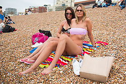 © Licensed to London News Pictures. 17/07/2016. Brighton, UK. ZSUZSANNA and PETRA from Hungary wont let the cloudy and grey skies spoil their day on the beach in Brighton. Photo credit: Hugo Michiels/LNP