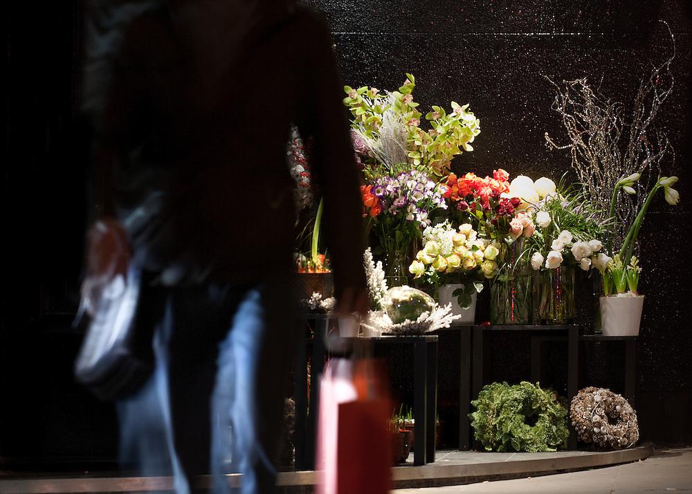 business man walking by florist near portman square in london at night