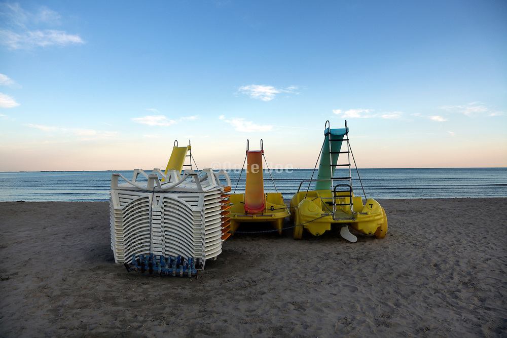 stack of folded lounge chairs on the beach with paddle boats