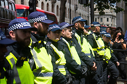 London, June 24th 2017. Anti-fascist protesters counter demonstrate against a march to Parliament by the far right anti-Islamist English Defence League. PICTURED: Police provide a formidable barrier between the two opposing groups.