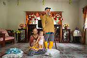 Fatimah Binti Jalal right - a smallholder palm oil farmer - stands with her daughter and grand-daughter in their home in Toniting, Beluran District, Sabah, Malaysia, on 8 September 2016. Fatimah has been farming her small plot since 2005, but the soil is sandy and not very productive. She has been able to increase her yields since becoming part of the Wild Asia Group scheme, which works with the Roundtable on Sustainable Palm Oil to support Malaysian smallholders to become certified sustainable. This includes improving farm management, reducing their use of pesticides and fertilizers, and increasing yields. Smallholders account for 40% of global palm oil production, and as such play an important role in increasing sustainability within the industry.
