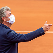 PARIS, FRANCE October 05. Chair umpire John Blom of Australia tosses the coin while wearing a mask before the match between Laura Siegemund of Germany and Paula Badosa of Spain in the fourth round of the singles competition on Court Simonne Mathieu during the French Open Tennis Tournament at Roland Garros on October 5th 2020 in Paris, France. (Photo by Tim Clayton/Corbis via Getty Images)