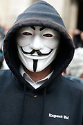 November 12th 2011 .  Protester at St Paul's, part of Occupy London wearing a Guy Fawkes mask , trademark of Anonymous movement and based on character in the film V for Vendetta. Words on his hoody say Expect Us.