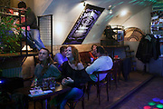 Moscow, Russia, 31/03/2012..Customers watching carnival music band Maracatu perform at the FAQ Cafe on television monitor.