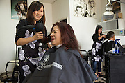 Helen Do gives Tina's Hair Design owner Tina Chang a blow dry at Tina's Hair Design in Milpitas, California, on September 11, 2014. (Stan Olszewski/SOSKIphoto)